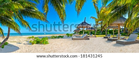Paradise beach in caribbean tropical with palms and parasol - stock photo