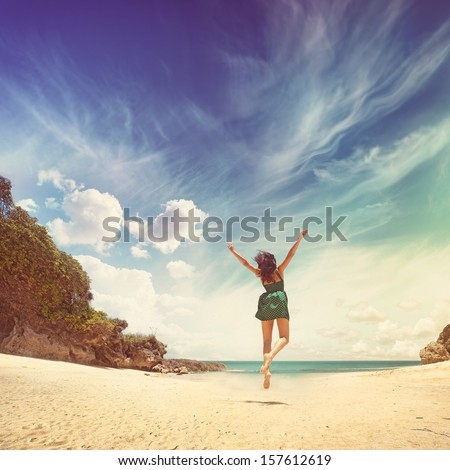paradise concept - woman jumping on a beach - stock photo