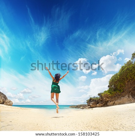 paradise concept - woman jumping on a beach