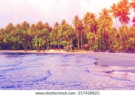 Paradise nature, sea and hotel house on the tropical beach in sunrise. Summer travel background with retro vintage instagram filter. - stock photo
