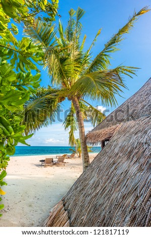 Paradise tropical island - view on hut, palm and ocean - stock photo