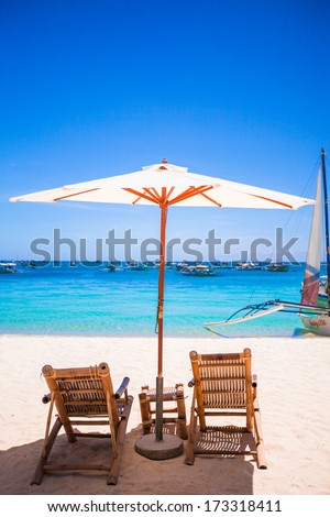 Paradise view of nice tropical empty sandy plage with umbrella and beach chair - stock photo