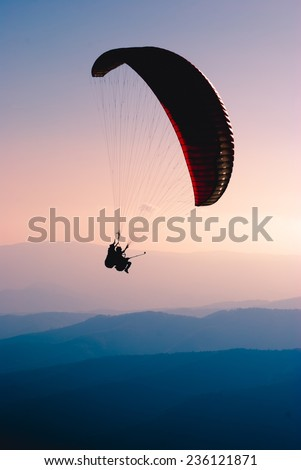 Paraglide in a sky over Carpathian mountains - stock photo