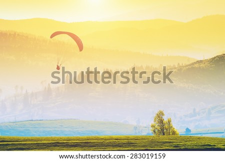 Paraglide silhouette flying over misty mountain valley in a warm light of sunrise. - stock photo