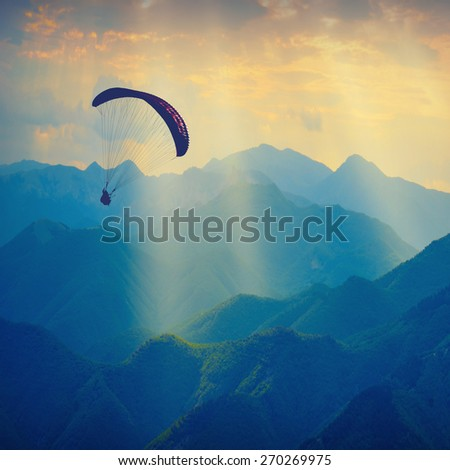 Paraglide silhouette flying over the mountain peaks. Beautiful rays of light in a high mountain valley. - stock photo