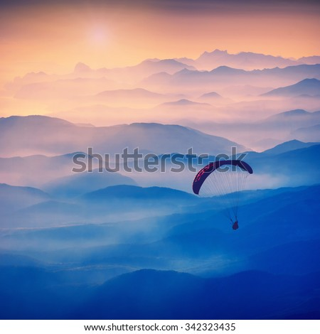 Paraglide silhouette in a light of sunrise above the misty Crimea valley. Vintage colors - stock photo