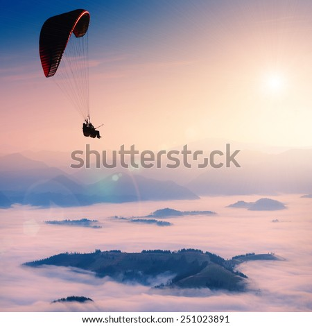 Paraglide silhouette over misty mountain valley. - stock photo