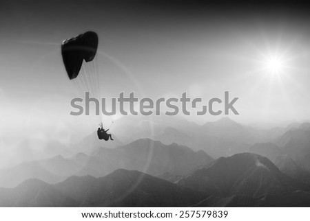 Paraglide silhouette over mountain peaks. Monochrome colors - stock photo