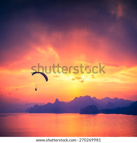 Paraglide silhouette over the sea sunset with beautiful reflection of sun light in water of Black sea. Crimea. Ukraine. - stock photo