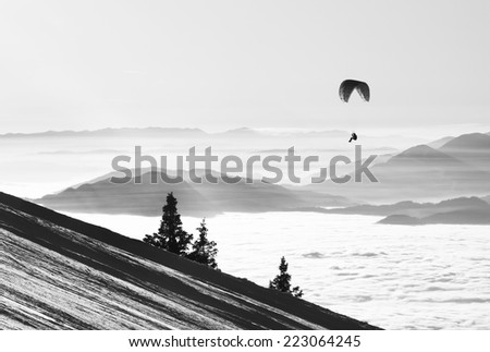 Paraglide silhouette shadow over Alps peaks and clouds - stock photo