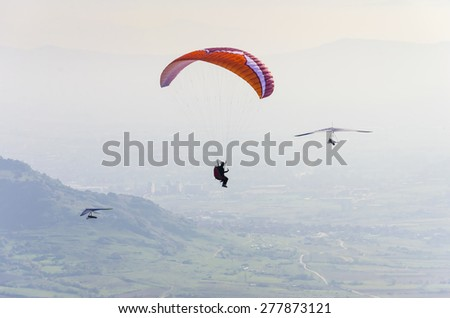 Paraglider and two pilot gliders - stock photo