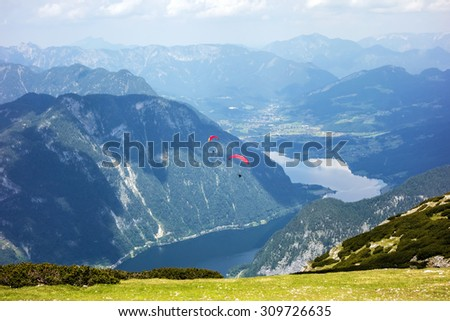 Paraglider at the sky over the Dachstein mountains - stock photo