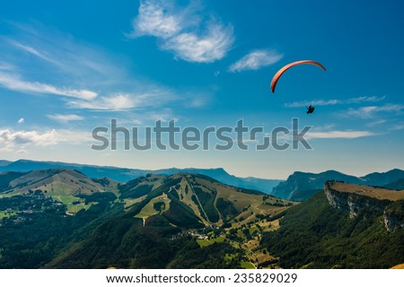 Paraglider flies over the Dolomites to infinity - stock photo