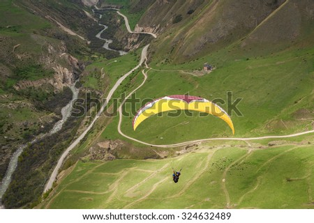 Paraglider flying aerial view - stock photo