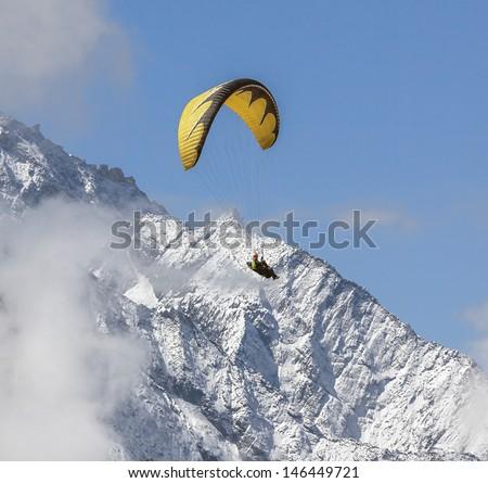 Paraglider flying against the mountain Lhotse (8516 m) - Everest region, Nepal, Himalayas - stock photo