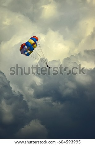 Paraglider flying in deep storm clouds