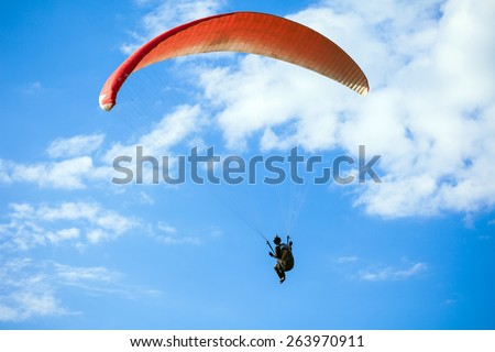 Paraglider flying on blue sky - stock photo