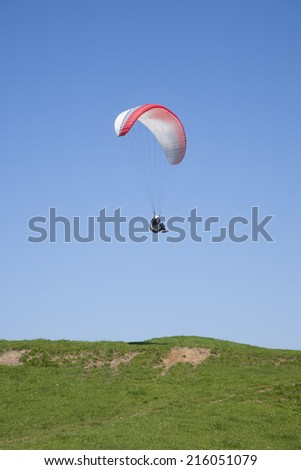 paraglider flying over green field in Asturias Spain - stock photo