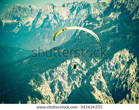 Paraglider flying over high and rugged range of Alps mountains. Cross process toned and Instagram stylized filtered stock photo with vignette. - stock photo