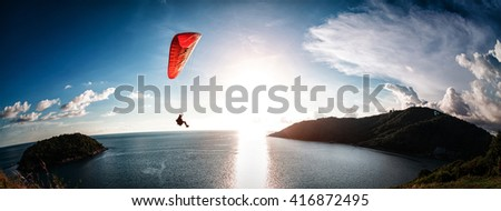 Paraglider flying over the water during sunset  - stock photo