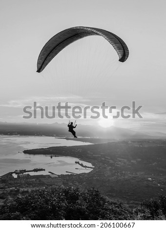 Paraglider flying over vespers Petropavlovsk-Kamchatsky on the background of the Avachinsky bay at sunset - Kamchatka, Russia (black and white)