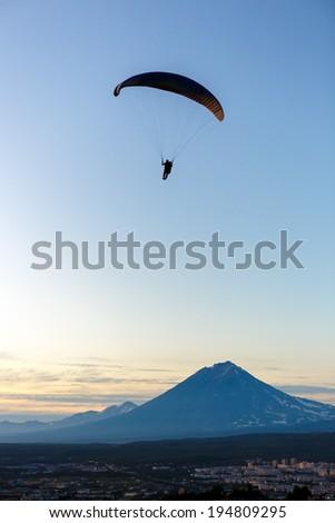 Paraglider flying over vespers Petropavlovsk-Kamchatsky on the background of the volcano Koryaksky at sunset - Kamchatka, Russia - stock photo