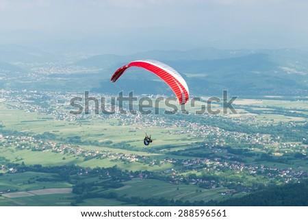 Paraglider flying over village in mountains in summer day. - stock photo