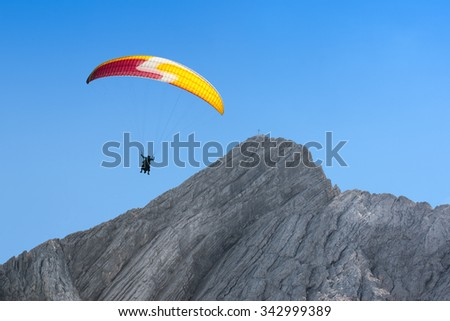 Paraglider free soaring at a great height in cloudless sky over dolomites Alps peak mount - stock photo