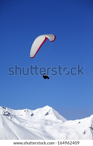 Paraglider in snowy winter mountains. Caucasus Mountains. Georgia, ski resort Gudauri.