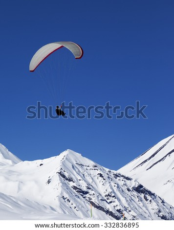 Paraglider in sunny snowy mountains at nice day. Caucasus Mountains. Georgia, ski resort Gudauri.