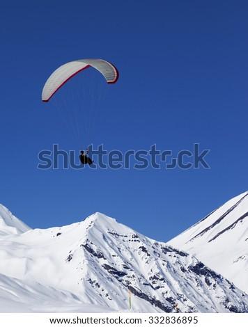 Paraglider in sunny snowy mountains at nice day. Caucasus Mountains. Georgia, ski resort Gudauri. - stock photo