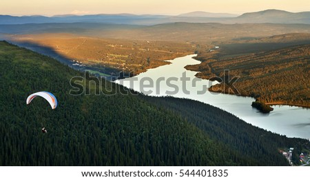Paraglider in the left corner flying over forest, a mountain landscape and a lake. Sweden.