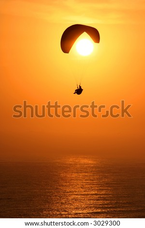 Paraglider infront of an amazing sunset in southamerica. Very warm colors and a bit of motion blur in the ocean.
