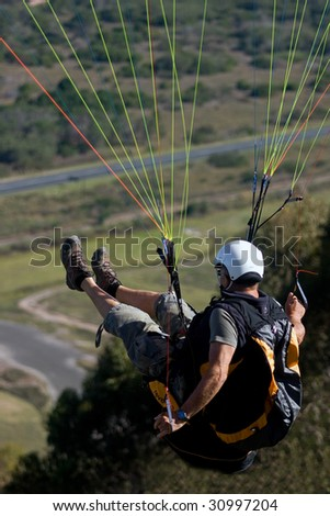 Paraglider jumping off hill and in the air just after lift off - stock photo