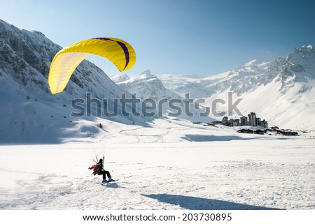 Paraglider landing on skis in Tignes, a ski resort in the french Alps - stock photo