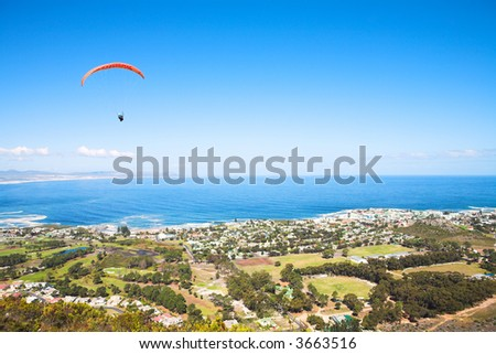 Paraglider launching from the ridge with an orange canopy against a blue sky. The town of Hermanus (Western Cape, South Africa) in the bottom of the screen - Editorial use only - stock photo