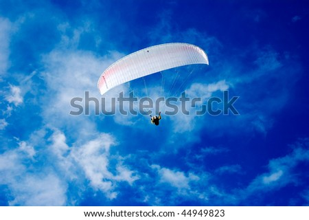Paraglider on amaizing blue sky with fantasy clouds - stock photo