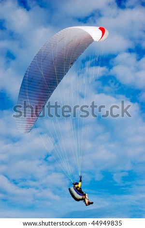 Paraglider on light blue sky with feather clouds vertical - stock photo