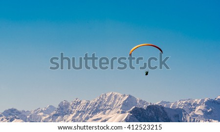 paraglider over austrian alps in winter - stock photo