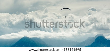 Paraglider over mountains and cloudy sky background - stock photo