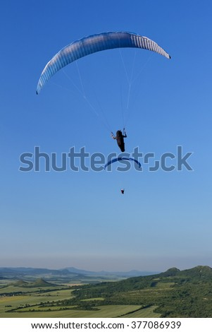 Paraglider. Parachuter. Paragliding in mountains. Paragliding sport.Parachute jumper.Parachute. Extreme sports activity. paragliding over the green valley - stock photo