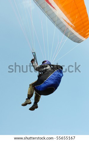 paraglider pilot flying against the blue sky
