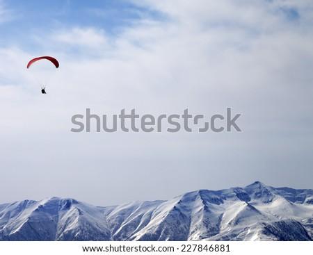 Paraglider silhouette of mountains in sunlight sky. Caucasus Mountains. Georgia, ski resort Gudauri. - stock photo