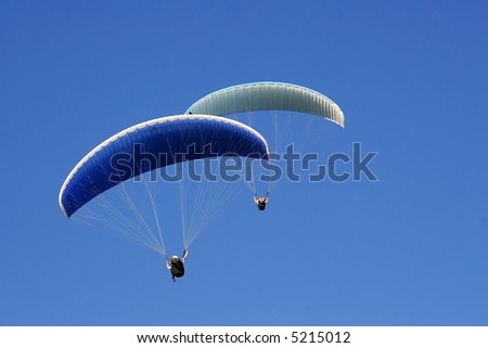 Paraglider soaring in a blue sky - stock photo