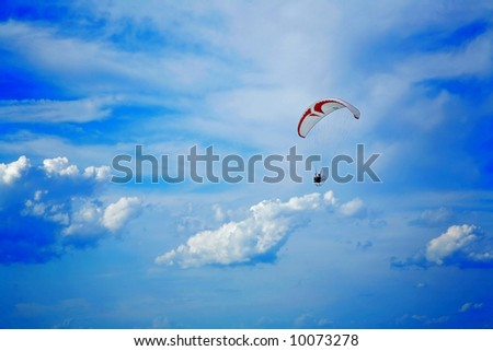 Paraglider soaring in blue summer sky - stock photo
