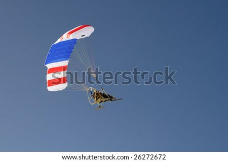 Paraglider with propelling flying in the sky
