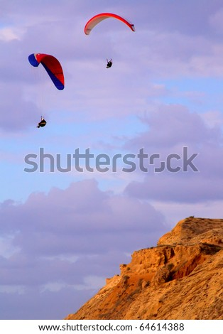 paragliders above beach head at sunset - stock photo