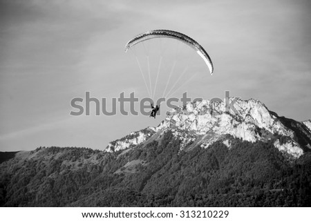 Paragliders flying in tandem and mountains of Savoy at background (Annecy Lake, France) . Aged photo. Black and white. - stock photo