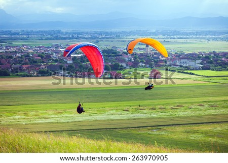 Paragliders flying over green fields with typical romanian village on background - stock photo