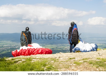 Paragliders in starting phase in front of the mountains. - stock photo